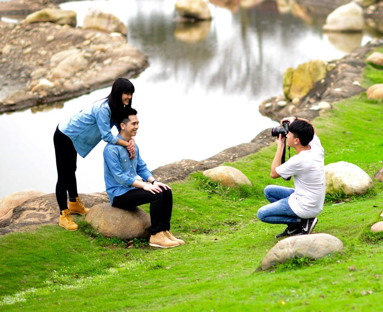 real people, two people, rock - object, leisure activity, sitting, togetherness, full length, water, casual clothing, grass, day, lifestyles, nature, women, outdoors, photography themes, men, camera - photographic equipment, photographing, beauty in nature, young women, friendship, young adult, people