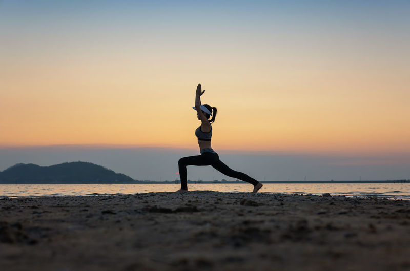 Side view of woman with arms raised exercising at beach against sky during sunset