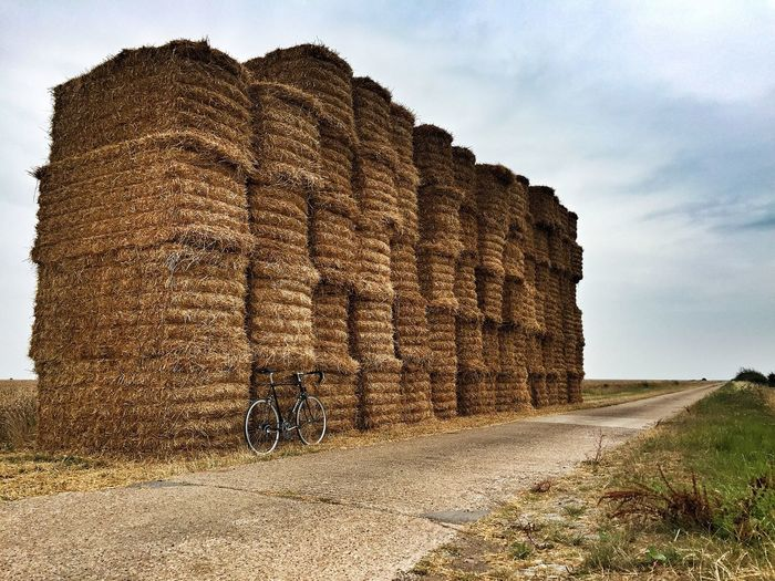 Bicycle parked by stacked hay