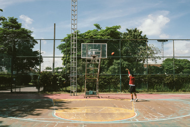 Ball Basketball - Ball Basketball - Sport Basketball Hoop Court Day Full Length Leisure Activity Men Motion Nature Outdoors People Plant Playing Real People Sky Sport Sunlight Tree