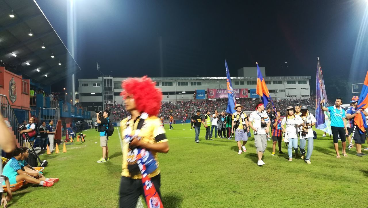 large group of people, sport, real people, men, leisure activity, night, performance, lifestyles, stadium, spectator, playing, arts culture and entertainment, togetherness, crowd, playing field, skill, sportsman, competition, grass, outdoors, audience, soccer field, teamwork, fan - enthusiast, sports team, people, adult, adults only