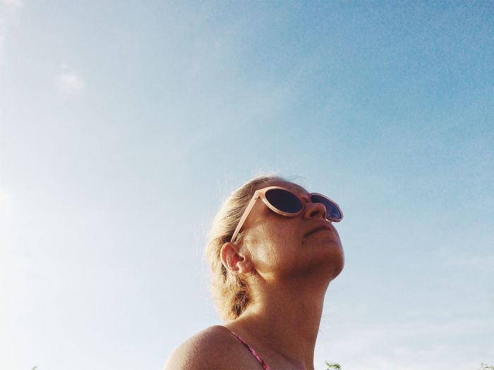 Low Angle View Of Woman In Sunglasses Against Clear Sky