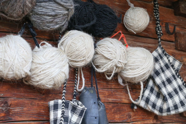 Close-up of wool balls hanging on wooden wall