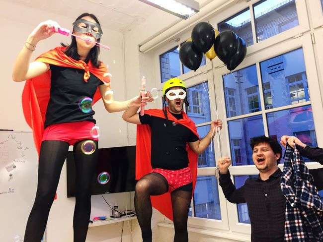 Fun Arms Raised Young Women Happiness Indoors  Cheerful Men Togetherness Christmas Party Superheroes Yawning Bubbles Helmet