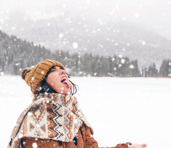 Young woman catching snowflakes with her mouth. winter, snow, outdoors.
