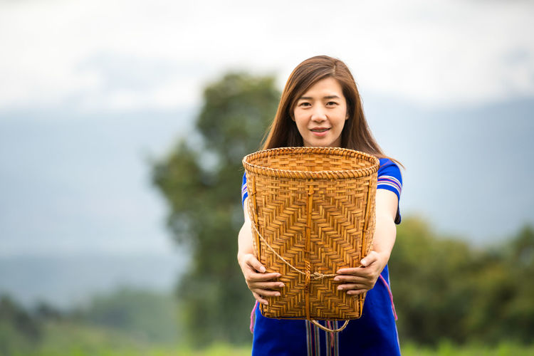 Portrait of smiling young woman holding basket