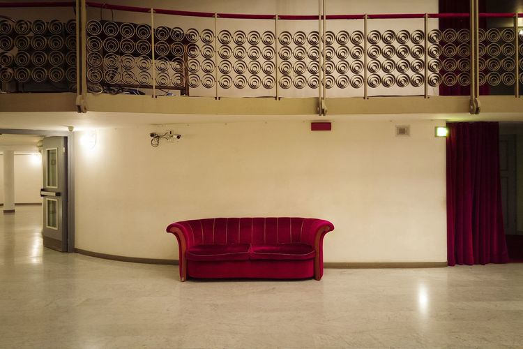 Empty red velvet couch at movie theater