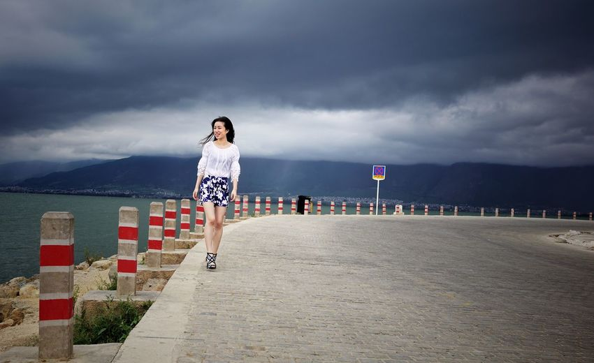 Woman walking along beach against cloudy sky