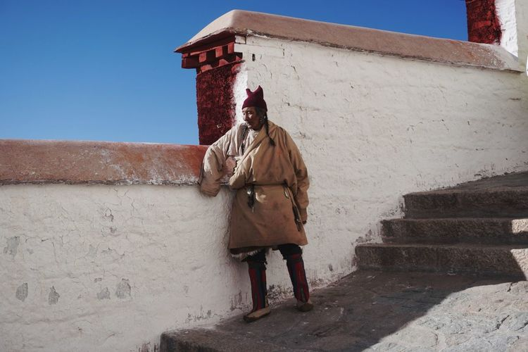 Full length of man standing against wall of building