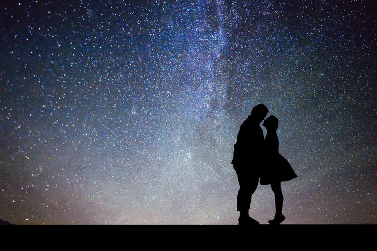 Side view of silhouette couple romancing while standing against star field at night