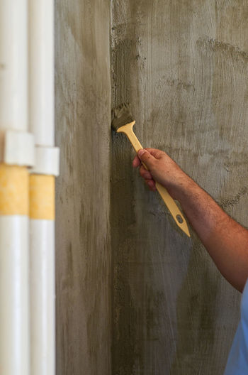 Man working on wood against wall