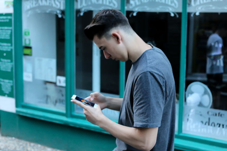 Side view of young man using mobile phone on street