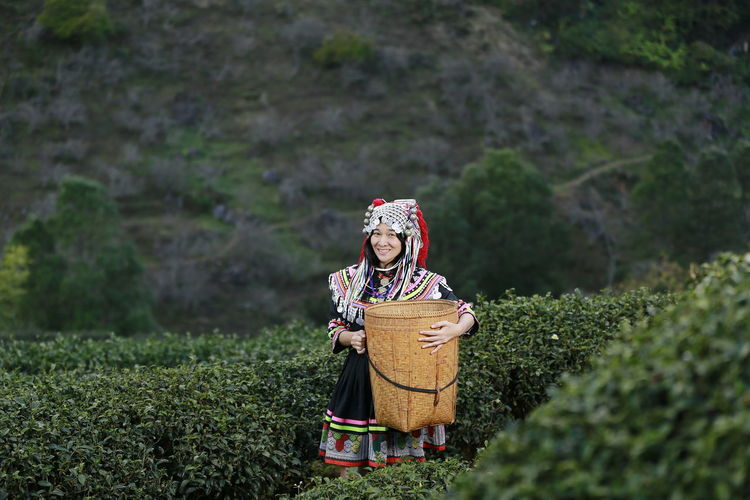 Portrait Of Smiling Woman With Wicker Basket Standing Amidst Tea Crops On Farm
