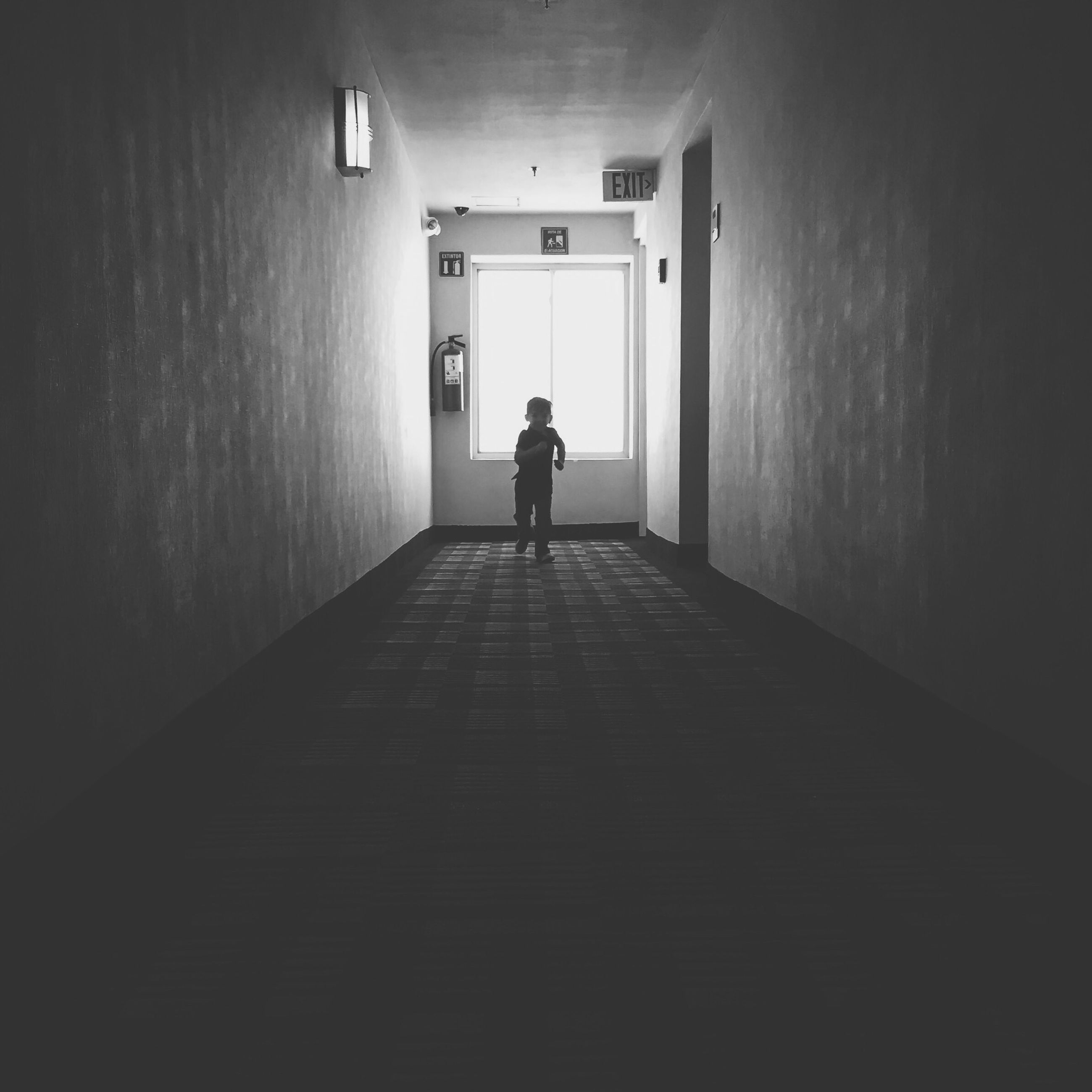 indoors, architecture, rear view, corridor, built structure, full length, lifestyles, men, the way forward, walking, standing, wall - building feature, wall, silhouette, person, leisure activity, door, building