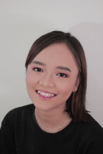 Portrait of a smiling young woman over white background