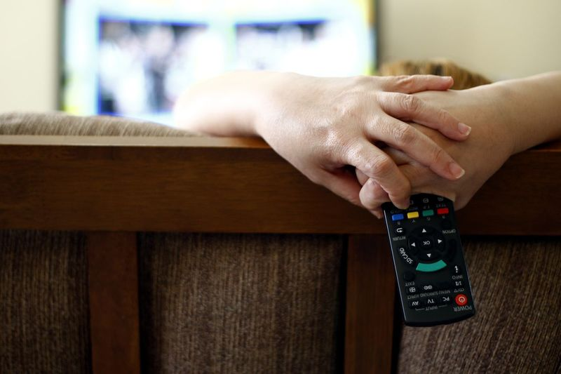 Woman Holding Remote While Watching Tv