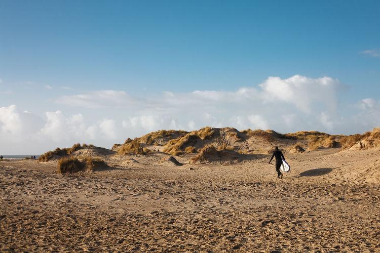 Rear view of man walking on arid landscape