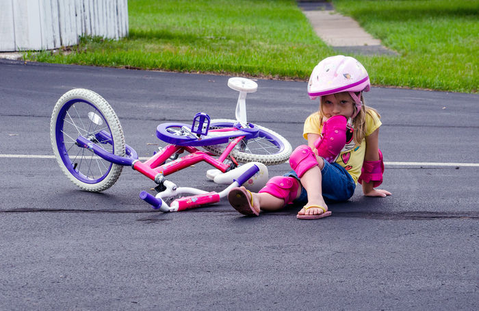 learning to ride a bike is not so easy, as this little girl finds out when she lands on the hard ground Accidents And Disasters Bicycle Bike Accident Bike Safety Casual Clothing Caucasian Child Childhood Cycling Helmet Falling Off Bicycle Full Length Girls Headwear Kid Learning To Ride A Bike Leisure Activity Lifestyles Outdoors Real People Safety Gear Training Wheels Transportation Visual Creativity Focus On The Story