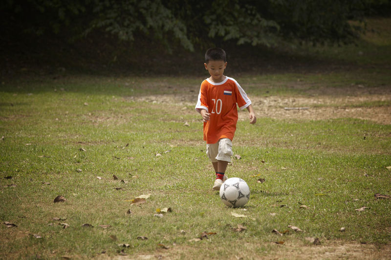 boy playing football Ball Boys Child Childhood Children Only Day Dribbling Full Length Grass Kicking Males  One Boy Only One Person Outdoors People Playing Running Soccer Soccer Ball Soccer Field Soccer Player Soccer Uniform Sport Sports Clothing Sports Uniform