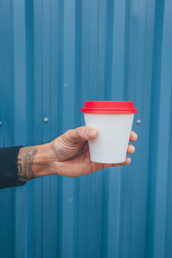 Cropped hand holding coffee against blue wall