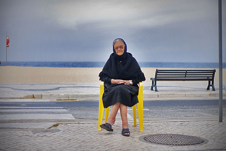 """(Early morning silence, a widow sits outside by the beach) Situated in the Portuguese Silver Coast, Nazare is a small fishing village in Portugal. Long an inspiration for many photographers and cinematographers, including a young Stanley Kubrik, Nazare has a very unique local culture intrinsically connected with the oceans with a long and rich sea tradition, embedded in local folklore. The Woman of Nazare ( Nazarena) for example, is the column that holds the community together and has been immortalised in monuments locally. When the men were at sea for months on end, the Woman of Nazare took care of family, business (usually selling fish and other sea produce) and everything else on land. This is even reflected in traditional attire. The """"7 skirts"""" (Sete Saias) for example, were in fact mostly work or utility aprons and shawls, exquisitely decorated and usually made by hand. When the men were returning from the sea with the catch, usually at night, the women would then be waiting on the beach and the aprons would turn to shawls becoming protective layers that they would wrap themselves with gradually as the cold set it. The sea was both the source of sustenance as well as of a lot of sorrow. Many women had lost husbands, sons and brothers at sea and many would trade in the colourful attire for black in mourning, a trait that it is still observed today. Some women continued their mourning to the end of their lives. Over the years, the fishing industry started to decline as both overfishing and the lack of interest of the younger generations in it, impacted local economy.. Nazare then turned to tourism as the main source of business, particularly in the Summer, season in which it is common for the locals to rent property to tourists over the summer (although nowadays, tourism is all year round, as Nazare became one of the best surfing destinations in the world, brought to world attention by surfer Garrett McNamara for it's 100ft waves at North Canyon, the deepest unde"""