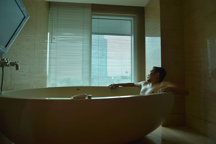 A man sitting in bathroom at home
