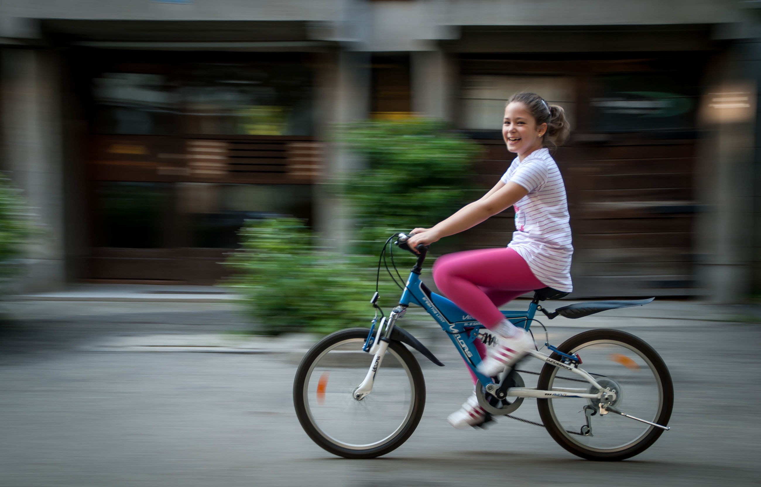 mode of transport, bicycle, transportation, blurred motion, motion, travel, land vehicle, on the move, riding, speed, full length, casual clothing, lifestyles, leisure activity, city life, holding, city, street, person, selective focus, looking at camera, outdoors, young adult, day