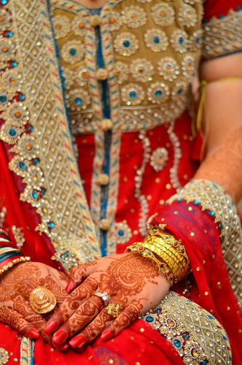 Close-up of bride with henna tattoo and red sari