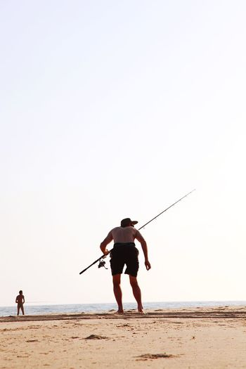 Rear view of man standing on beach against clear sky