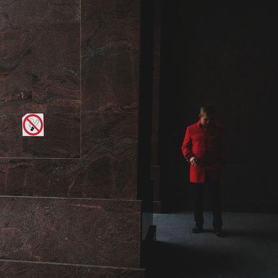 Man standing by red door
