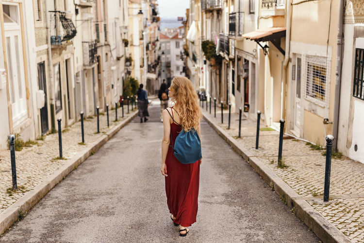 Woman walking against house