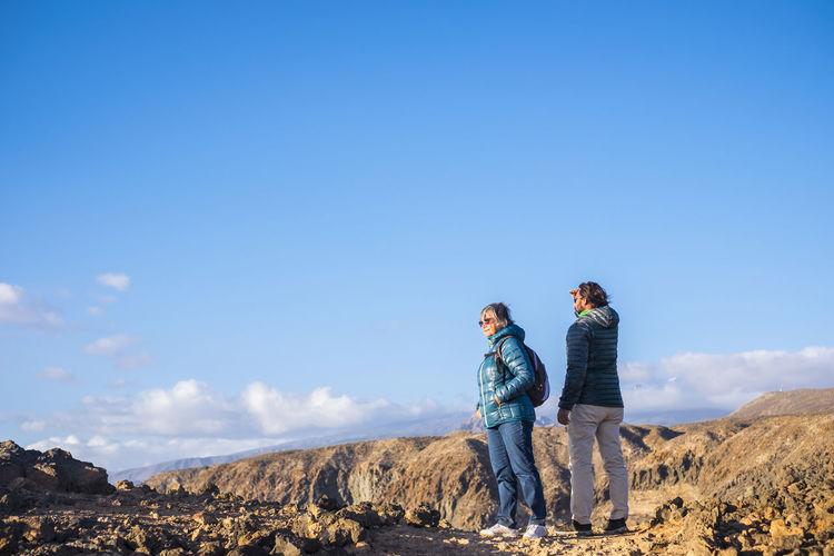 Hikers standing on landscape against blue sky