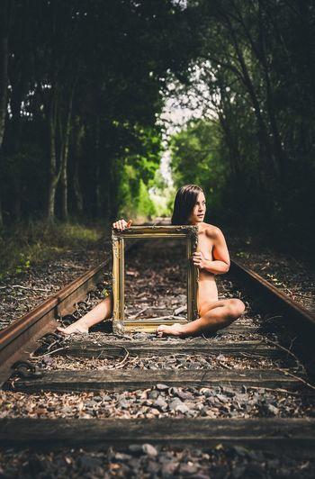 Full length of naked woman with mirror sitting on railroad track at forest