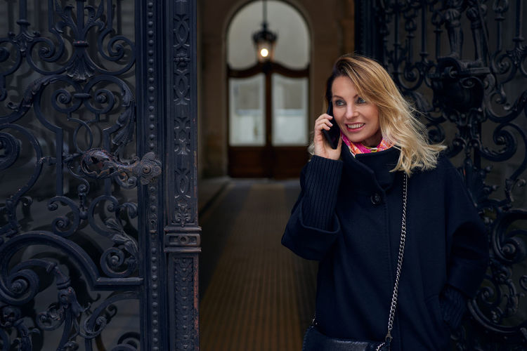 Attractive blond middle-aged woman talking on her cellphone Attractive Best Ager Blond Blond Hair Calling Cellphone Chatting Copy Space Doorway Front View Lifestyle Mobile Phone Smart Phone Smiling Standing Talking Upper Body Walking Woman