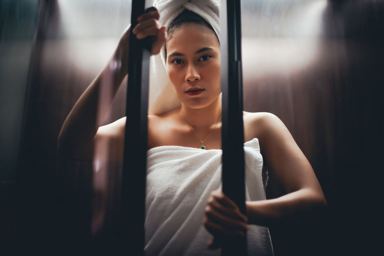 Portrait Of Young Woman Wrapped In Towels Standing By Railing
