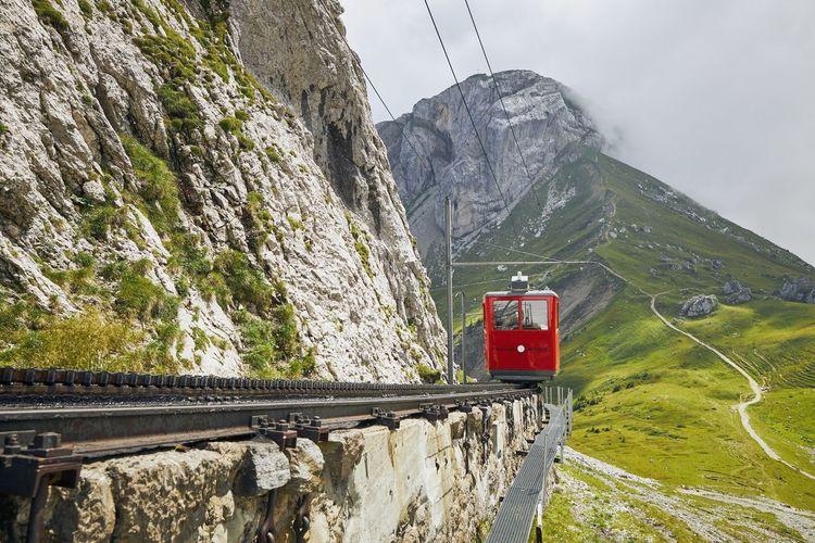 Overhead cable car over rocky mountains against sky