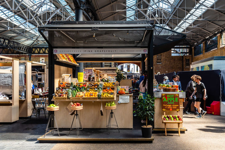 Old Spitalfields market with unidentified people. Fruits stall. The market hosts arts and craft and street food market. Brexit Britain London Uk Antique Architecture Beautiful British Building Business City Culture Destination England English Europe European  Flea Food Foodie Fruits Gastro Handcrafted Interior KINGDOM Landmark Market Marketplace Merchandise Old People Retail  Retro Revival Shop Shopping Shoreditch Spitalfields Stall Store Street Street Food Tourism Tourist Town Travel Vintage Whitechapel