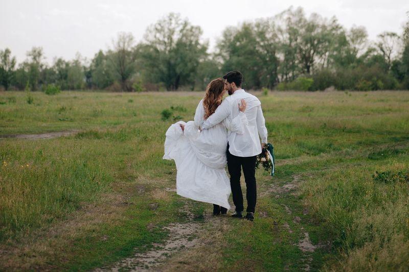 Newlywed couple walking on field against sky