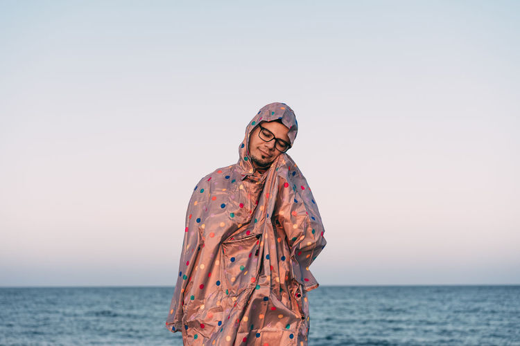 Person standing in raincoat by sea against clear sky