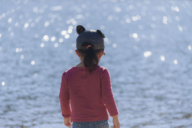 Rear view of girl standing against sea at beach