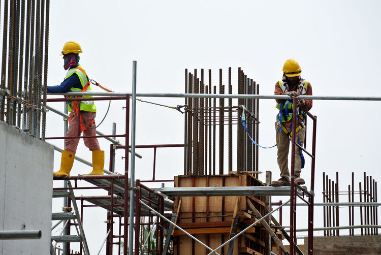 Workers at construction site against sky