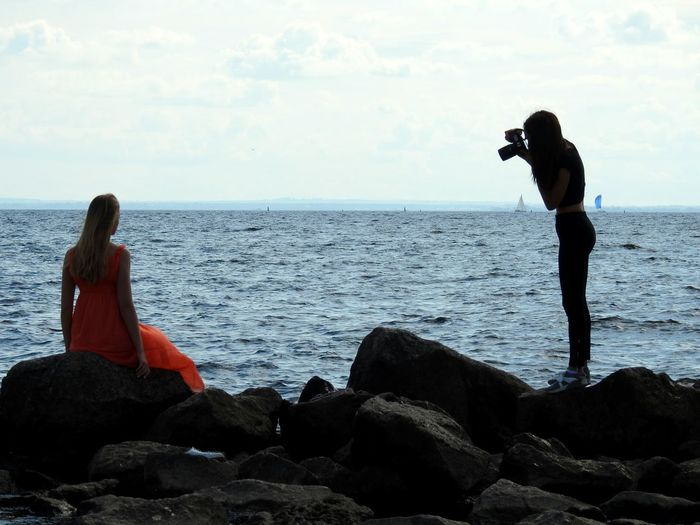Woman photographing model on shore