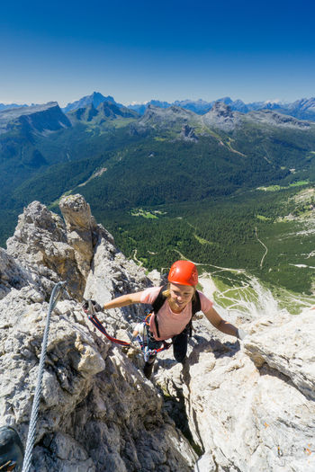 High angle view of woman climbing mountain against clear blue sky