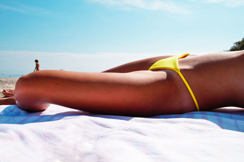Midsection Of Woman Lying On Towel At Beach During Sunny Day