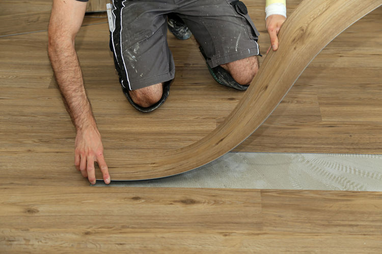 Low section of man working on hardwood floor at home