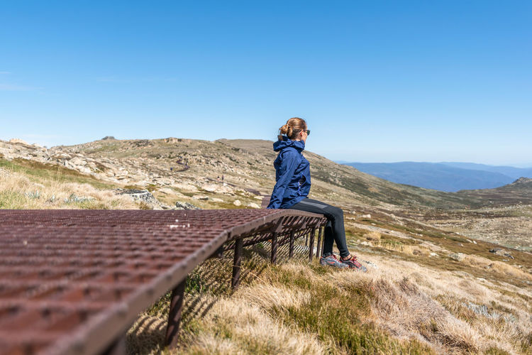Woman sitting on mountain against blue sky
