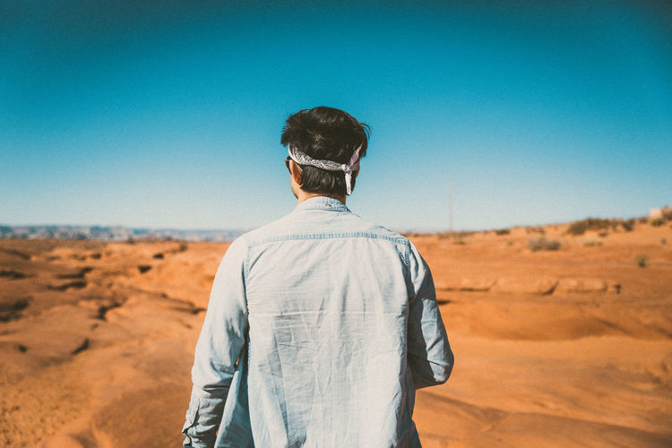 Rear view of man on desert against clear sky