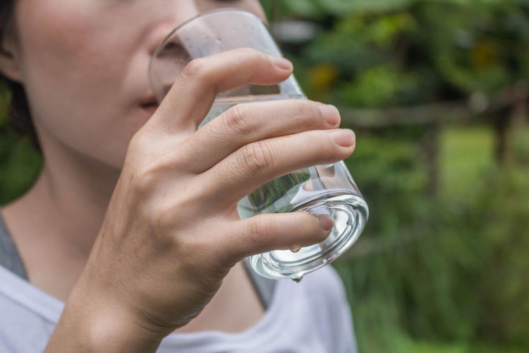 Midsection of woman drinking water