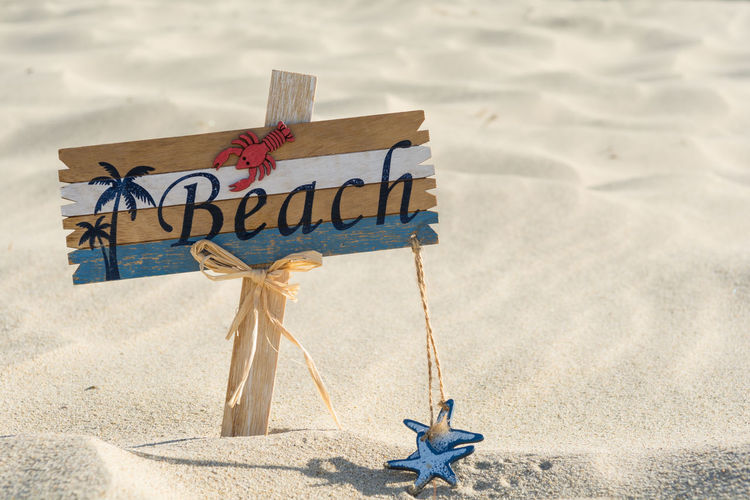 Wooden beach sign on the sand Signage Swimming Vacations Weathered Word Backgrounds Banner Beach Billboard Coast Communication Dune Label Old Sand Sandy Sea Sign Signboard Signpost Starfish  Summer Symbol Text Wooden