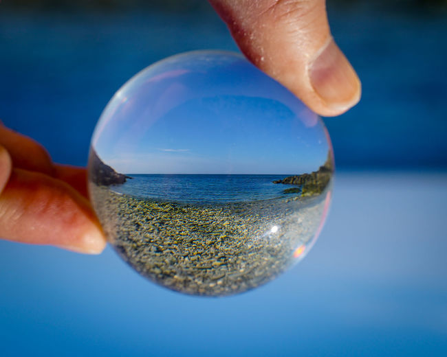 Close-up of hand holding crystal ball against sea and sky
